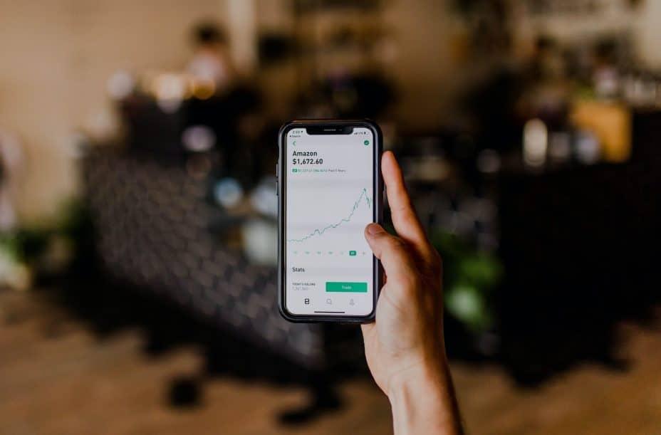 hand holding smartphone showing amazon stocks