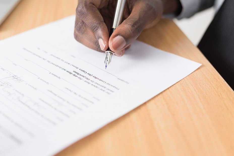 hand signing a contract — generic visual to illustrate how escrow fits into the transaction process.