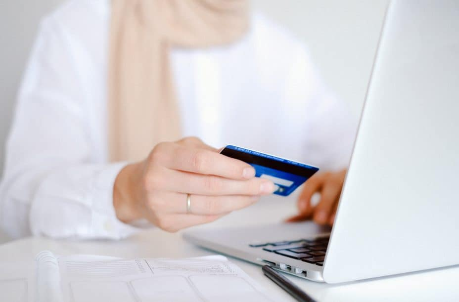 popular online business model 1 - eCommerce   Image: woman holding a credit card in front of a laptop
